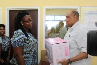 Minister Trotman hands over the sewing machine to a representative of the Home Economics Department.