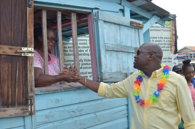 Minister Patterson interacts with residents during a brief walkthrough of a part of the village.