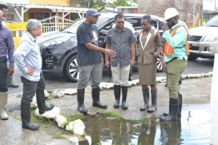 Minister within the Ministry of Public Infrastructure, Jaipaul Sharma, [left] and Mayor of Georgetown, Ubraj Narine [third from left] along with officials from the CDC and M&CC during their assessment of the city following heavy rainfall.