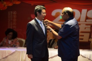 Prime Minister Nagamootoo pins on a golden pin on one of the doctors of the 14 Chinese Medical Brigade