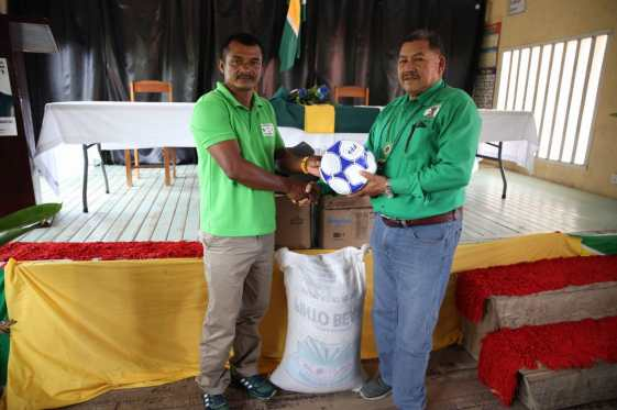 Minister of Indigenous Peoples' Affairs, Hon. Sydney Allicock handing over sports gear to a representative from the village