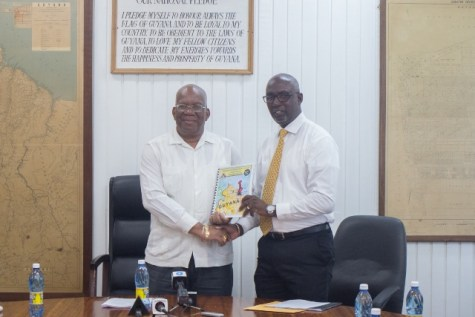 Minister of Finance, Winston Jordan receiving the Financial Intelligence Unit's (FUI) 2018 report from FIU's Director, Matthew Langevine.