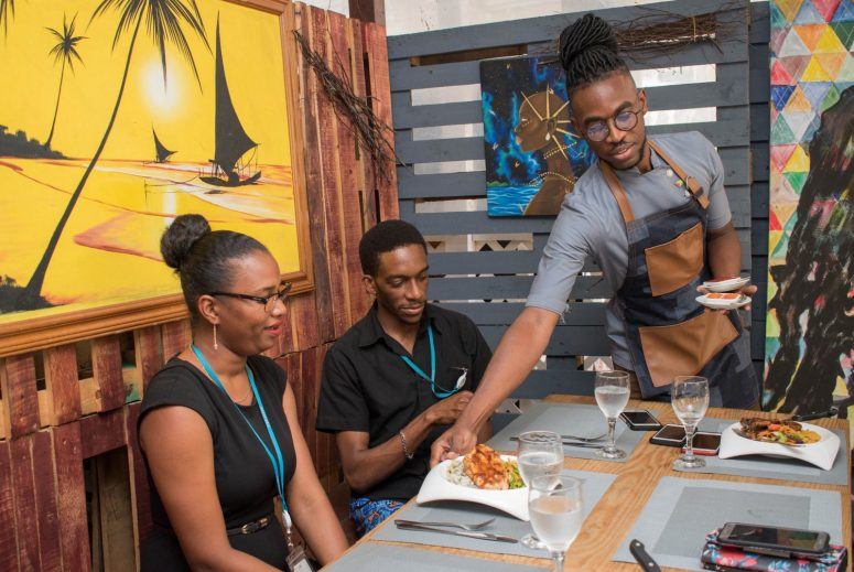 Kester Robinson serves a meal to his customers