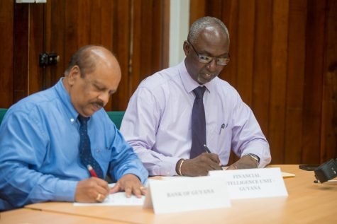 FIU head, Matthew Langevine signs MOU with Central Bank Governor, Dr. Gobind Ganga.
