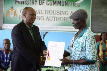 Director-General of the Ministry of the Presidency, Joseph Harmon hands over a title to a resident