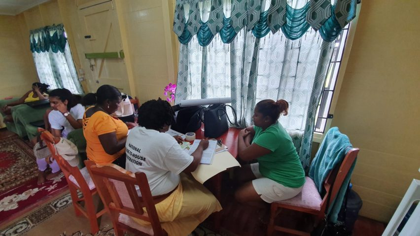 Michelle Biswah in green seated at the table with the GECOM enumerator and APNUAFC scrutineer during her registration process