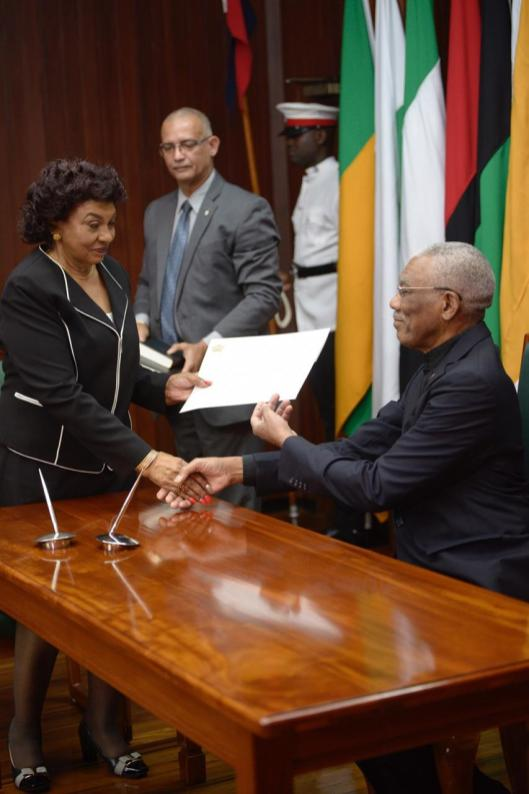 Justice Claudette Singh SC, CCH receives her instruments of office from His Excellency, President David Granger.