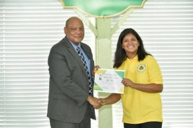 Minister of Natural Resources, Mr. Raphael Trotman presents a certificate of participation to an apprentice.