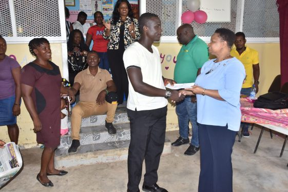 Community Health Worker, Baracara Health Centre, Kevon Joseph receives a token of appreciation from Minister of Public Health, Hon. Volda Lawrence