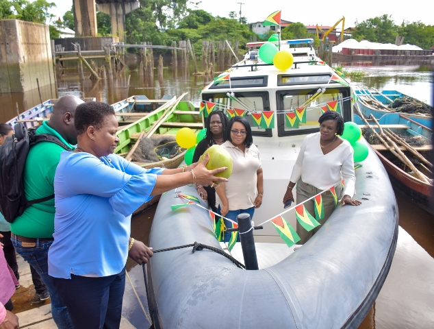 Minister of Public Health, Hon. Volda Lawrence officially commissions the Water Ambulance by pouring the ceremonial coconut water on the vessel.