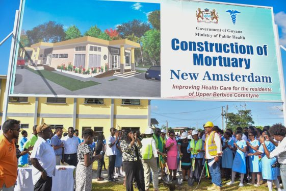 Ministry officials, representatives from Andre Vincente Construction Services and staff of the New Amsterdam Regional Hospital stand below a sign board with the Artist's impression of the multi-million-dollar mortuary which is being constructed