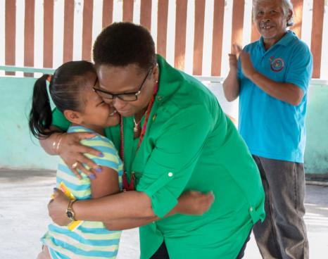 Public Health Minister, Hon. Volda Lawrence being greeted by a little girl from the community of Princeville in Region 8. In the background is volunteer Lloyd Henrito