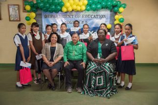 Minister of Indigenous Peoples' Affairs, Hon. Sydney Allicock pose with the region's top ten. Seated right is the Regional Education Officer, Keane Adams and Deputy Regional Executive Officer Ms. Audrey Gomes
