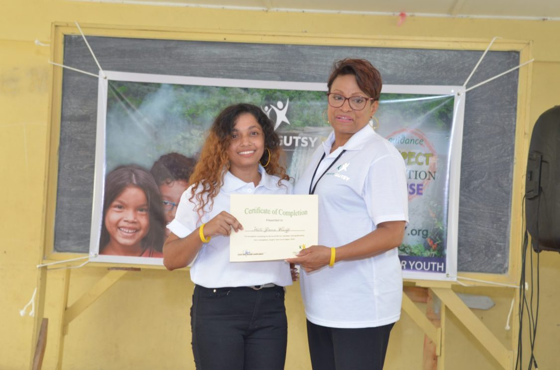 President of GUTSY, Janice Hall presenting a certificate of completion to one of the facilitators