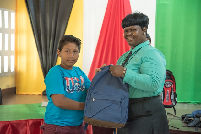 A primary school student receiving backpack from Education cadet Officer.