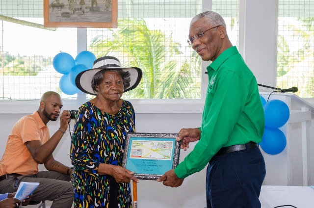 H.E President David Granger accepts a commemorative stamp from Victoria's oldest resident, Evelyn Bacchus.