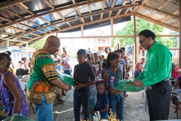 Minister of Finance,Hon. Winston Jordan and Minister of Legal Affairs, Hon. Basil Williams SC., distributing school bags to Litchfield's school children.