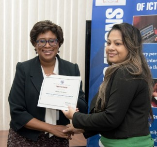 Minister of Public Telecommunications, Hon. Catherine Hughes, hands over a certificate to a participant who participated in the National Capacity Building on Web Accessibility program.