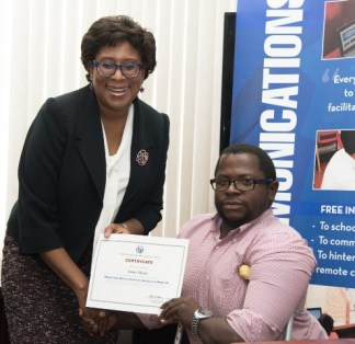 Minister of Public Telecommunications, Hon. Catherine Hughes, hands over a certificate to Jaime Skeete for participating in the National Capacity Building on Web Accessibility program.