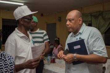 Minister of Natural Resources, Hon. Raphael Trotman listening to Campbellville resident, Ivor Anderson following a community meeting