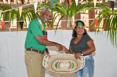 President David Granger shares a warm handshake and smile with this resident after she presented him with a token on behalf of the village.
