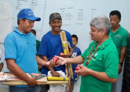 Minister Sharma present cricket gear to members of the Potarinau club.