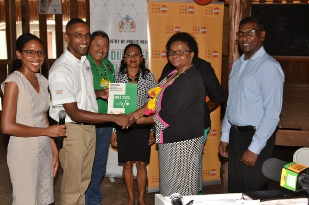 UNFPA Liaison Officer, Adler Bynoe hands over the new National Sexual Reproductive Health Policy to Minister of Public Health, Hon. Volda Lawrence. Also, in the picture from left is, Minister of Indigenous Peoples Affairs, Hon. Sydney Allicock, Toshao of Pakuri Village, Beverley Clenkian, Regional Chairman of Demerara-Mahaica, Genevieve Allen and Chief Medical Health Officer, Dr. Shamdeo Persaud.
