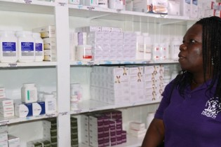 Clinical Coordinator, Ministry of Public Health, Caroline Hicks inspects stocks of drugs at a health facility.