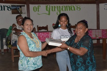 Minister of State, Hon. Dawn Hastings-Williams handing over a tablet to Mary Edwards on behalf of her grand daughter