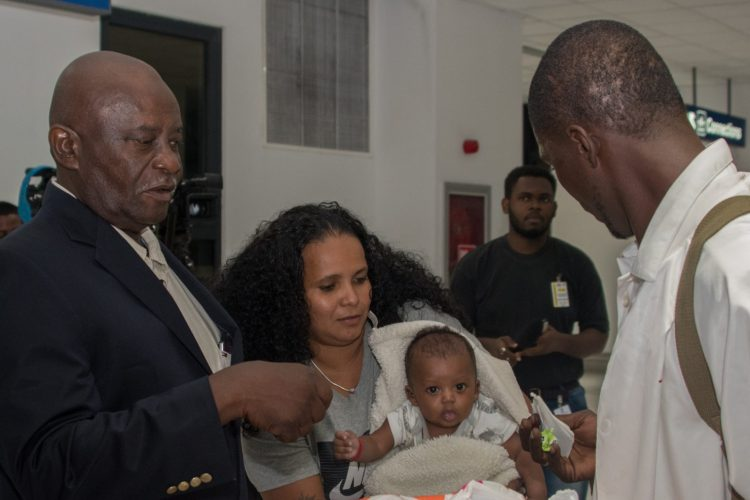 Minister of Citizenship, Hon. Winston Felix welcoming the Cooper family to Guyana at the Cheddi Jagan International Airport (CJIA)