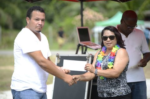 Minister of State, Hon. Dawn Hastings-Williams handing over the land permit to President of the Speightland Logging and Agriculture Cooperative, Kevon Lorrmier