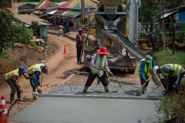 Workers compacting concrete just beyond Port Kaituma Police Station.