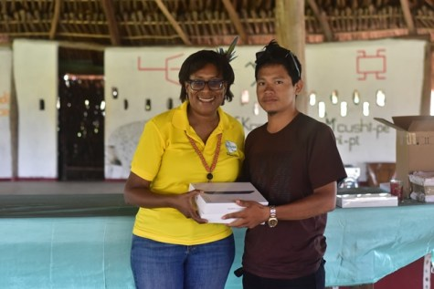 Minister Catherine Hughes hands over a tablet to Brenrick Francis, a youth leader in the Kumu Village