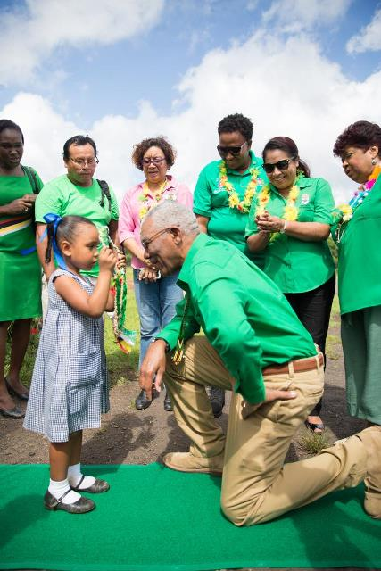 President David Granger being welcomed by little Eudisha Williams of Port Kaituma