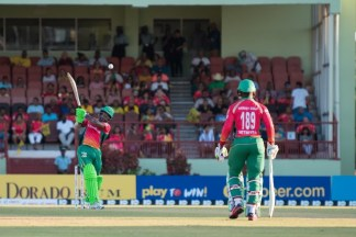 Chanderpaul Hemraj as he smashed the ball for a massive six, as teammate Shirmon Hetymer looks on.