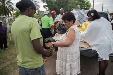 Minister of Social Protection, Hon. Amna Ally distributing items to the residents.
