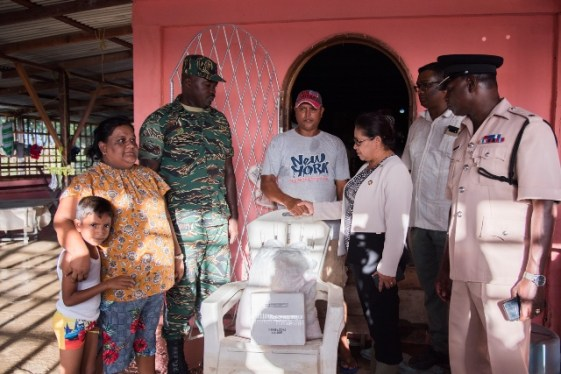 Minister of State, Hon. Dawn Hastings-Williams, Civil Defence Commission and Regional Information Officer, Ganesh Mahipaul hands over hamper to the Persauds family.