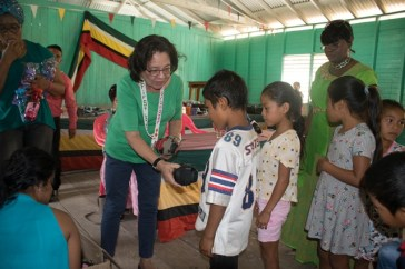 First Lady, Her Excellency, Sandra Granger distributing footwear to some children.