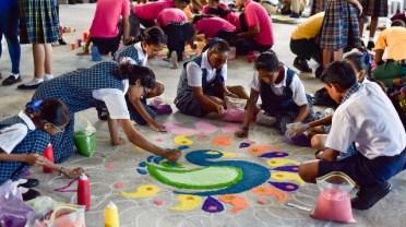 Students of Mae's School working on their rangoli.