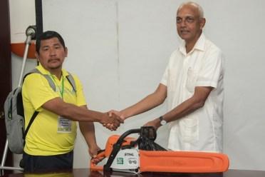 Minister of Communities, Hon. Ronald Bulkan handing over the chainsaw to Senior Councillor of Quatata, Joseph Dorrick.