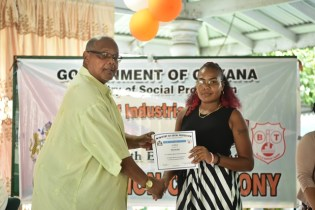 BIT graduate Emanuella Belle receives her certificate from Vice Chairman of BIT Donald Ainsworth.