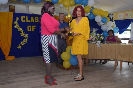 Elizabeth Persaud receives a trophy from Headmistress Sharon Savory on behalf of her daughter Devanie Persaud who was the second-best graduating student