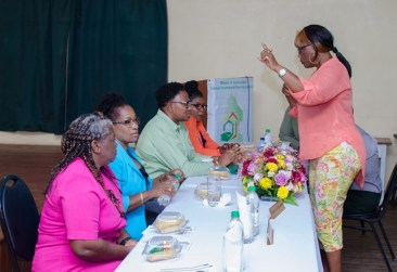 Minister within the Ministry of Communities, with responsibility for Housing, Hon. Annette Ferguson interacting with a resident.
