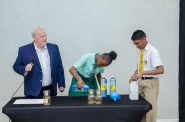 Richard Boyce overseeing an experiment by the high school students form Kingston Secondary School and Queen's College.