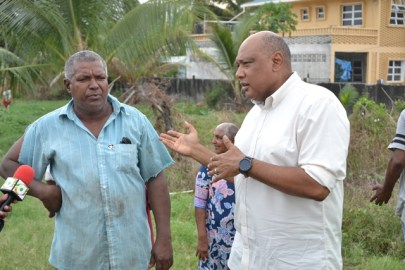 Minister of Natural Resources, Hon. Raphael Trotman speaking with resident Lloyd Alphonso.