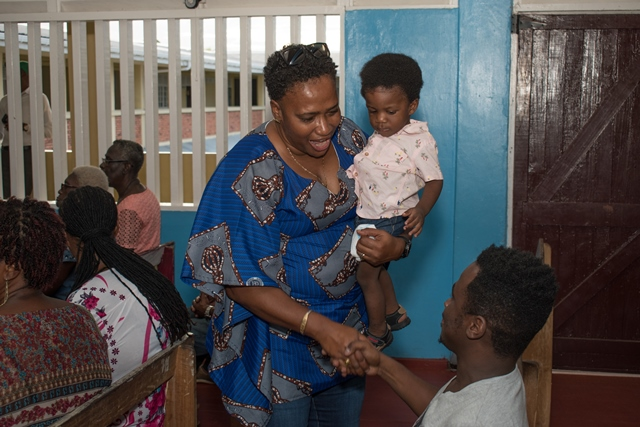 Minister within the Ministry of Communities, with responsibility for Housing, Hon. Annette Ferguson greets a resident of South Ruimveldt while she cradles a little one in her arms.