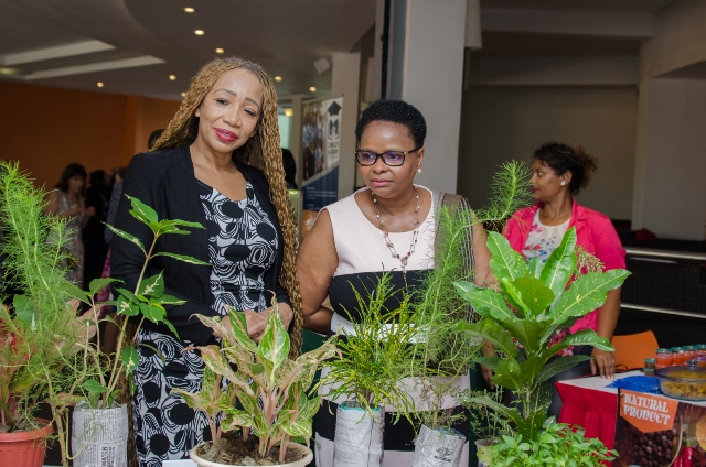 Minister of Public Health, Hon. Volda Lawrence [right] is given a tour by Sonia Noel [left] of the varying booths