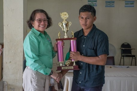 Her Excellency, First Lady, Sandra Granger hands out a trophy for the most improved graduate - Orlando Andrews.