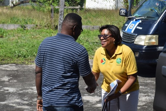 Minister of Public Telecommunications, Hon. Catherine Hughes being welcomed by one of the villagers of Queenstown.