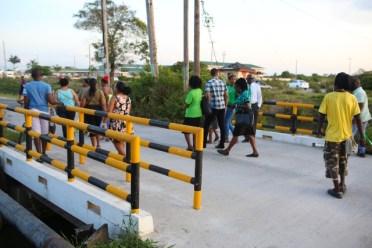 Residents cross the new bridge linking Roxanne Burnham Gardens to Rasville